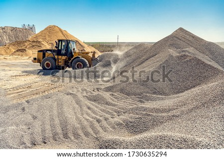 A large powerful loader overloads a pile of rubble in a concrete plant. Royalty-Free Stock Photo #1730635294