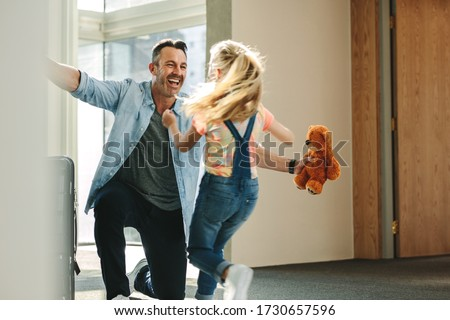 Girl running towards her father at the entrance door holding a teddy bear. Daughter meeting her father just arrived from a business trip. Royalty-Free Stock Photo #1730657596
