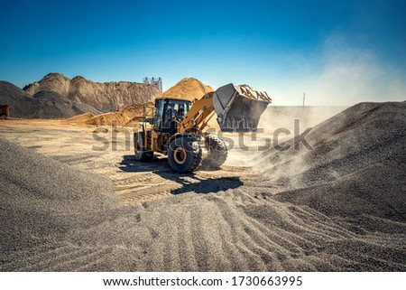 A large powerful loader overloads a pile of rubble in a concrete plant. Royalty-Free Stock Photo #1730663995