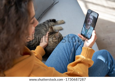 Young hispanic latin teen girl relax sit on sofa with cat at home holding phone video calling distance friend dating online on mobile screen using smartphone videochat app. Over shoulder closeup view Royalty-Free Stock Photo #1730687287