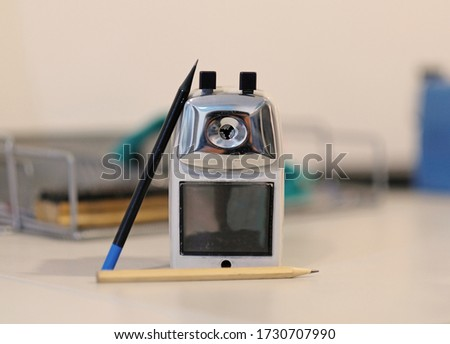 Pencil sharpener and two pencils. Focus on pencil sharpener.