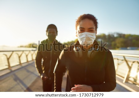 Jogging during quarantine. Young african couple wearing face medical masks while running together on the bridge in the morning. Sport and coronavirus. Covid-19. Protection. Social distancing #1730712979
