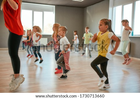 Group of little boys and girls dancing while having choreography class in the dance studio. Female dance teacher and children dancing. Contemp dance. Hip hop. Kids and sport. Full length #1730713660