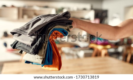 Cropped shot of hand of woman holding stack of colorful t shirts while standing in the store. Clothes at custom T-shirt, clothing printing company. Horizontal shot