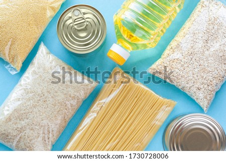 Set of grocery items from pasta, rice, oatmeal, couscous, oil and canned food on blue background. Food delivery, donation or stock provision concept. Top view, flat lay.