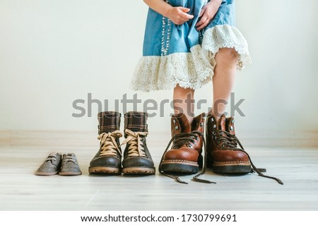 Close up of little girl in  dress putting on father's hiking shoes. Father's, mother's and kids boots standing in a row indoor. Family concept. Selective focus on the boots. #1730799691