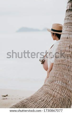 Beautiful asian young pregnant woman wearing orange bikini is  standing to take a picture by the sea at Phangan island in evening time. Selective focus and split color.
