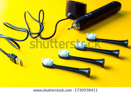 Modern rechargeable sonic or electric toothbrush set with usb charger and heads on yellow flat lay background. Concept of professional oral care and healthy teeth by using ultrasonic toothbrush