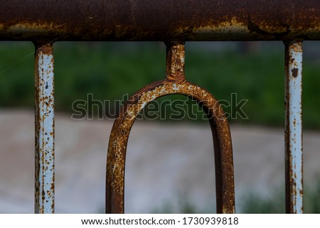 Rust on metal. Fragment of a rusty metal fence made of rods. Rust on welding parts. Red rusty stains on iron. Rust texture. Macro photo. Abstract grunge background #1730939818