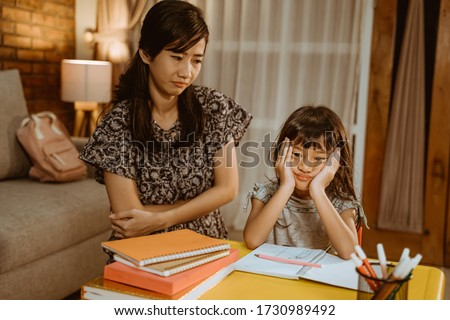 tired kid doing homework in the evening with mother