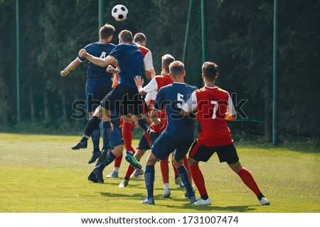 Soccer players heading the ball in competition. Football adult game. Players in two teams compete for the ball. Footballers jumping high on the grass pitch #1731007474