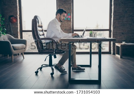 Profile side view of his he nice attractive chic confident focused man qualified IT expert economist sitting in chair preparing report at modern loft brick industrial style interior workplace station Royalty-Free Stock Photo #1731054103