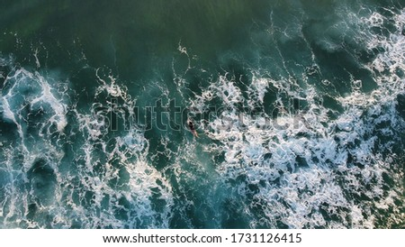 Aerial view, drone shot of a surfer paddling out to sea as waves crash leaving beautiful patterns in the water, stunning colours
