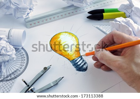 Designer drawing a light bulb, concept for brainstorming and inspiration #173113388