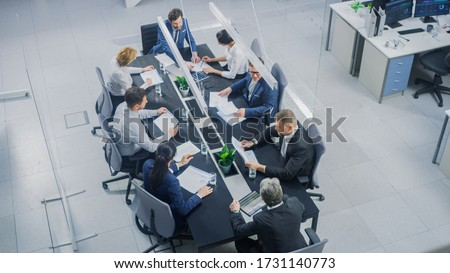 In the Corporate Office Meeting Room Group of Businesspeople, Investors, Executives and Members of the Board of Directors Talking, Negotiating and Working on a Winning Strategy. High Angle Shot Royalty-Free Stock Photo #1731140773