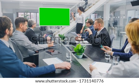 In the Corporate Meeting Room: Female Speaker Uses Digital Chroma Key Interactive Whiteboard for Presentation to a Board of Executives, Lawyers, Investors. Green Mock-up Screen in Horizontal Mode