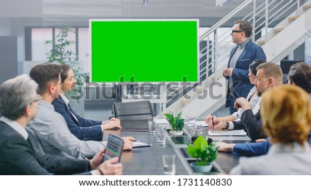 In the Corporate Meeting Room: Creative Director Uses Digital Chroma Key Interactive Whiteboard for Presentation to a Board of Executives, Lawyers, Investors. Green Mock-up Screen in Horizontal Mode
