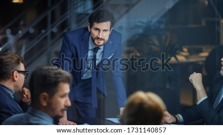 Corporate Meeting Room: Confident and Handsom Executive Director Decisively Leans on a Conference Table and Delivers Report to a Board of Executives about Company's Record Breaking Revenue Royalty-Free Stock Photo #1731140857