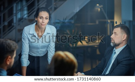Corporate Meeting Room: Confident and Beautiful Female Executive Director Decisively Leans on the Conference Table and Delivers Report to a Board of Executives about Company's Record Breaking Revenue Royalty-Free Stock Photo #1731140860