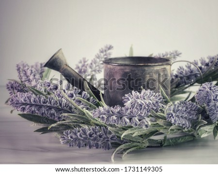 A closeup picture of vintage watering pot decorated with purple lavender against a grey background