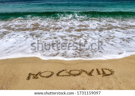 """""""No covid"""" written on the sand of the shore of a beach with incoming waves. Fear of beach resort managers for the upcoming summer season due to the coronavirus covid-19 #1731159097"""