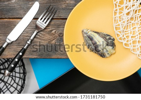 Yellow and black plates with a fork and knife on a wooden table. Oyster shell in a yellow plate. Top view with a space for text. Concept of a postcard, calendar or picture