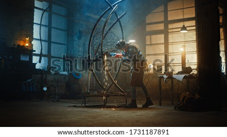 Young Contemporary Female Artist is Grinding Her Metal Tube Sculpture with a Handheld Power Tool in a Studio Workshop. Empowering Woman Makes Modern Brutal Abstract Artwork Out Of Metal. Royalty-Free Stock Photo #1731187891