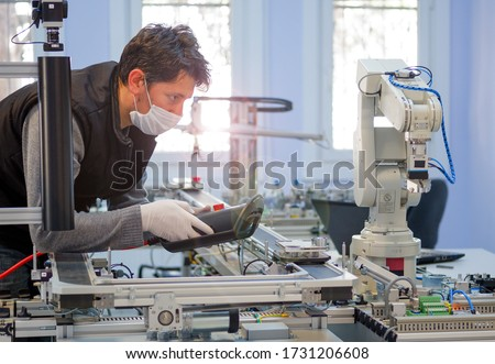 Man with surgical mask on face against COVID-19 ( Coronavirusis ) programming robot arm with control panel which is integrated on smart factory production line. industry 4.0 automation line. #1731206608