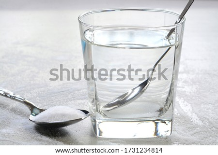 Salt water in a glass cup and salt in a teaspoon. Salt water has high level of minerals and salt water gargle helps in removing of cold and sore throat #1731234814