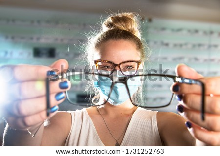 Beautiful young Optical Assistant wearing a face mask showing a pair of glasses  #1731252763