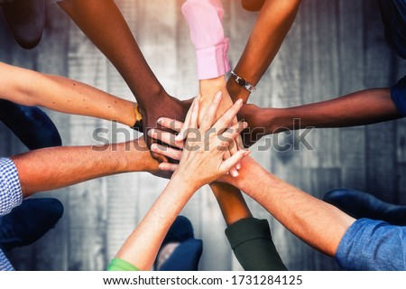 Close up view of young business people putting their hands together. Stack of hands. Unity and teamwork concept. #1731284125