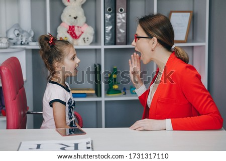 Cute little girl at speech therapist's office. Small child practicing articulation with therapist at private lesson at home. Royalty-Free Stock Photo #1731317110