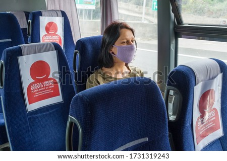 COVID-19 Public bus traveling during the coronavirus pandemic. Woman wearing protective mask while traveling by bus with new social distancing protect rules during pandemic of coronavirus in Italy #1731319243