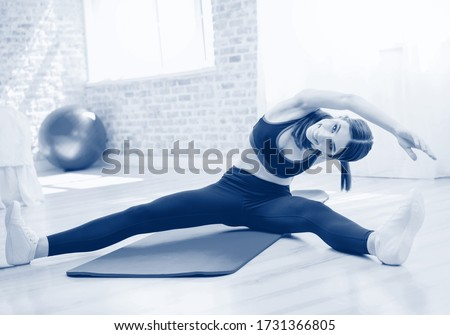 Happy smiling brunette girl in sportswear, doing fitness exercise, indoors. Healthy lifestyle, weight lossing and sporting theme concept. Black and white monochrome blue tone picture.