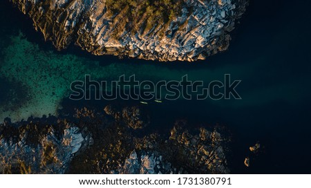 Aerial picture of kayaks between islands. Active summer vacation, north of norway located in lofoten islands. Two people kayaking surrounded beautiful landscape and turquoise sea. Distance picture