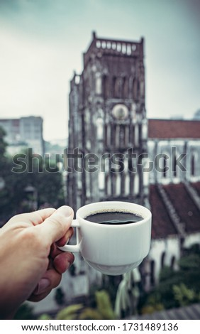 coffee Cup in hand against the background of a Catholic Church in Hanoi