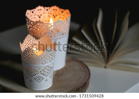 Two candle holders with lit candles and open book on a table. Selective focus, dark and cosy atmosphere. #1731509428