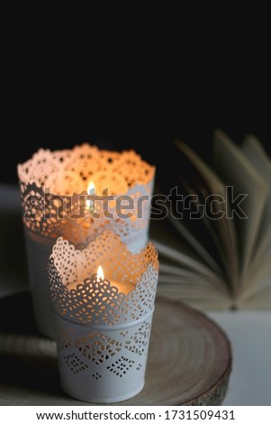 Two candle holders with lit candles and open book on a table. Selective focus, dark and cosy atmosphere. #1731509431