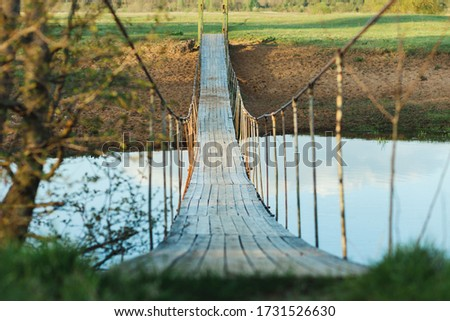 Old suspended wooden foot bridge over the river. Photo on a summer day. River crossing for people #1731526630