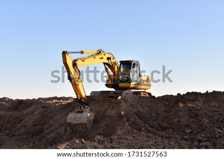 Yellow excavator during earthmoving at open pit on blue sky background. Construction machinery and earth-moving heavy equipment for excavation, loading, lifting and hauling of cargo on job sites Royalty-Free Stock Photo #1731527563
