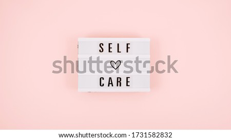 Self-care word on lightbox and flower narcissus on pink background flat lay. Take care of yourself Royalty-Free Stock Photo #1731582832