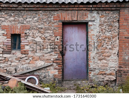 a picture of the authentic brick barn with contrast looking door of pale red color painted in peeled aged paint