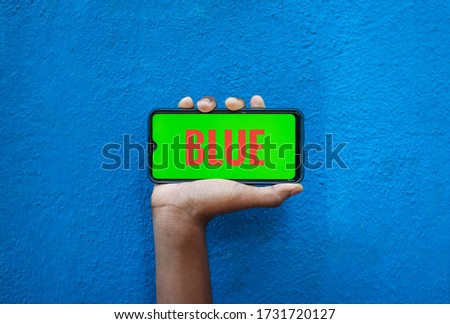 Blue word on orange color in smart phone screen isolated on blue background with copy space for text. Person holding mobile on his hand and showing front of the screen word blue.