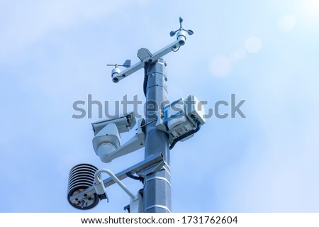 Automatic weather station, with a weather monitoring system and video cameras for observation. Against the background of blue sky clouds. Royalty-Free Stock Photo #1731762604