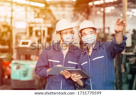Engineer teamwork worker wearing disposable face mask or face shield during working in factory to prevent Covid-19 virus air dust pollution and for good hygiene. #1731770599