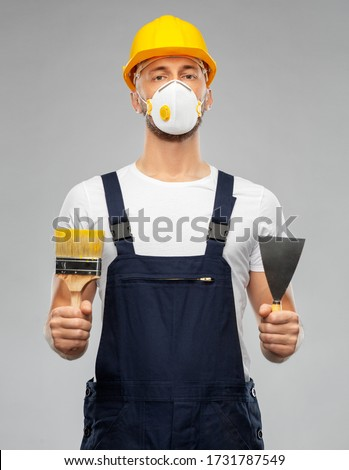 repair, construction and building - male worker or builder in helmet and respirator mask with paint brush and putty knife over grey background Royalty-Free Stock Photo #1731787549
