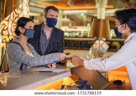 Couple and receptionist at counter in hotel wearing medical masks as precaution against virus. Young couple on a business trip doing check-in at the hotel Royalty-Free Stock Photo #1731788119