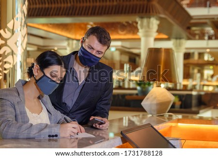 Couple and receptionist at counter in hotel wearing medical masks as precaution against virus. Young couple on a business trip doing check-in at the hotel #1731788128