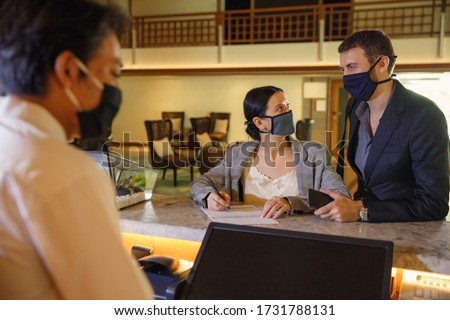 Couple and receptionist at counter in hotel wearing medical masks as precaution against virus. Young couple on a business trip doing check-in at the hotel #1731788131