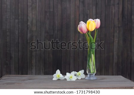 A bouquet of pink and yellow tulips in a glass vase on a old wooden background near with narcissus. #1731798430